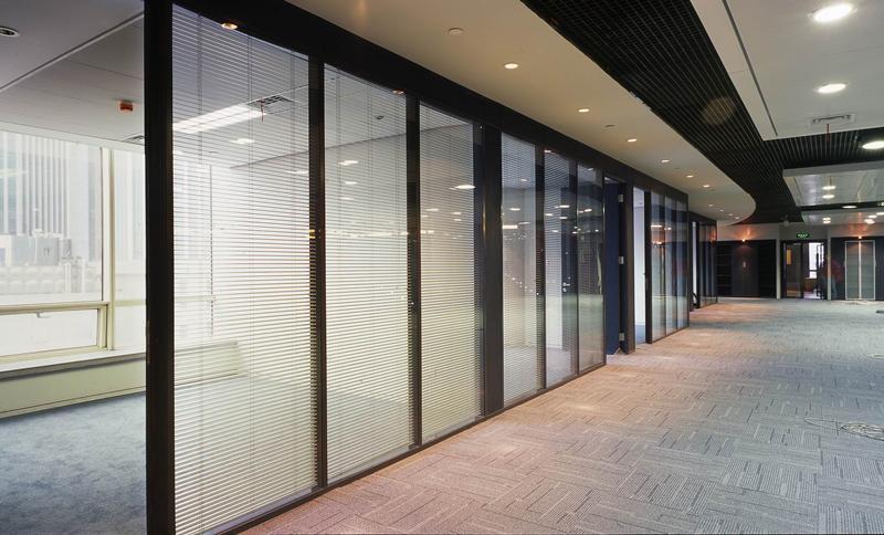 办公窗帘大致分为:卷帘、百叶帘、垂帘。 卷帘分为:半遮光、全遮光。 百叶帘分为:横百叶、竖百叶、材质丰富如;铝制、PVC、木质、竹质等等。 垂帘:较为高档,可分为普通窗帘和哈拉斯帘。 下面小编带大家看几款几款常用办公室窗帘: 用在玻璃隔断内的办公百叶帘:  可采用绳杆一体式控制也可采用电动控制;更加清爽方便,用作这样的全玻璃式隔断办公再好不过了! 会议室卷帘:  卷帘操作简单方便,具有外表美观简洁,使得窗框显得干净利落,让整个房间看上去宽畅明亮。 办公垂直帘:  垂帘一般比较常用在接待方面的接待厅会客厅。